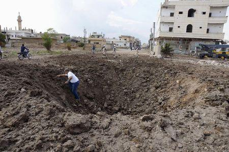 A man walks out of a crater caused by what activists said was a barrel bomb dropped by forces loyal to Syria's President Bashar Al-Assad in the town of Dael, north of Deraa