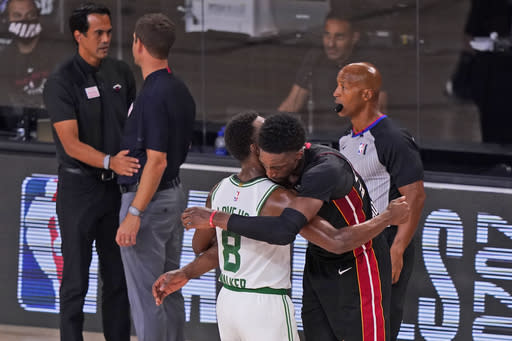 Miami Heat's Bam Adebayo, right, hugs Boston Celtics' Kemba Walker (8) as Miami Heat head coach Erik Spoelstra, top left, greets Boston Celtics head coach Brad Stevens after the Heat's win over the Celtics in an NBA conference final playoff basketball game Sunday, Sept. 27, 2020, in Lake Buena Vista, Fla. (AP Photo/Mark J. Terrill)