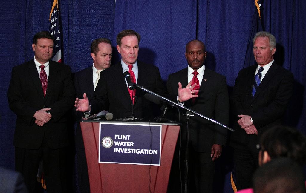 Michigan Attorney General Bill Schuette stands at the podium with (L-R) Chief Investigator Andy Arena, Special Prosecutor Todd Flood, Deputy Chief Investigator Ellis Stafford and Geneses County Prosecutor David Leyton on April 20, 2016 (AFP Photo/Bill Pugliano)