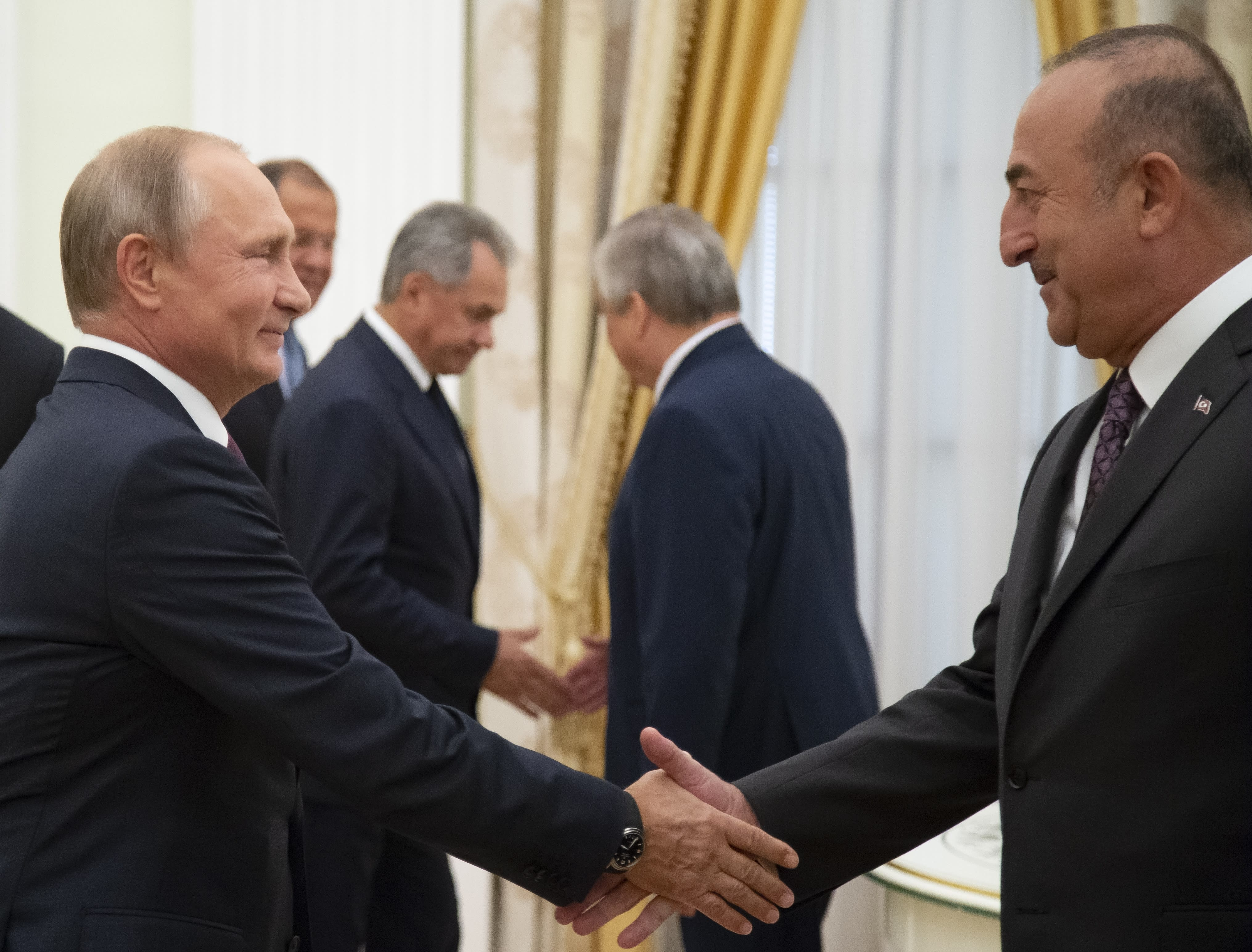 Russian President Vladimir Putin, left, shakes hands with Turkish Foreign Minister Mevlut Cavusoglu during their meeting in the Kremlin in Moscow, Russia, Friday, Aug. 24, 2018. Turkey's Foreign Minister on Friday warned against a possible Syrian government offensive on the last remaining stronghold of opposition against President Bashar Assad, while Russia indicated that it's losing its patience with the rebels. (AP Photo/Alexander Zemlianichenko, Pool)
