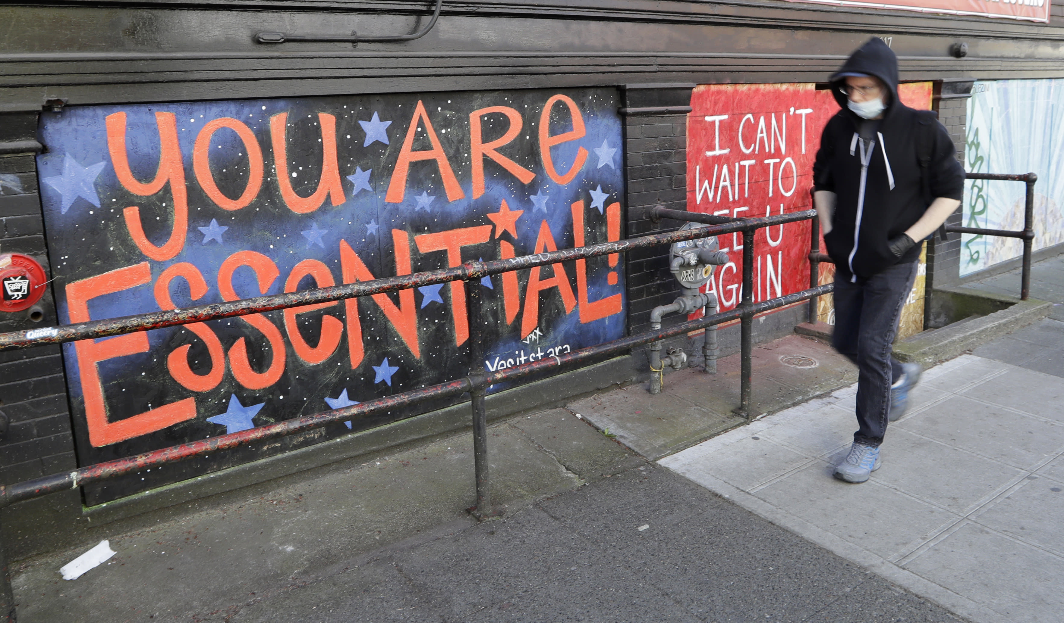 FILE - In this Thursday, April 16, 2020 file photo, a pedestrian walks past artwork painted on plywood covering a business closed during the coronavirus outbreak in Seattle. (AP Photo/Elaine Thompson)