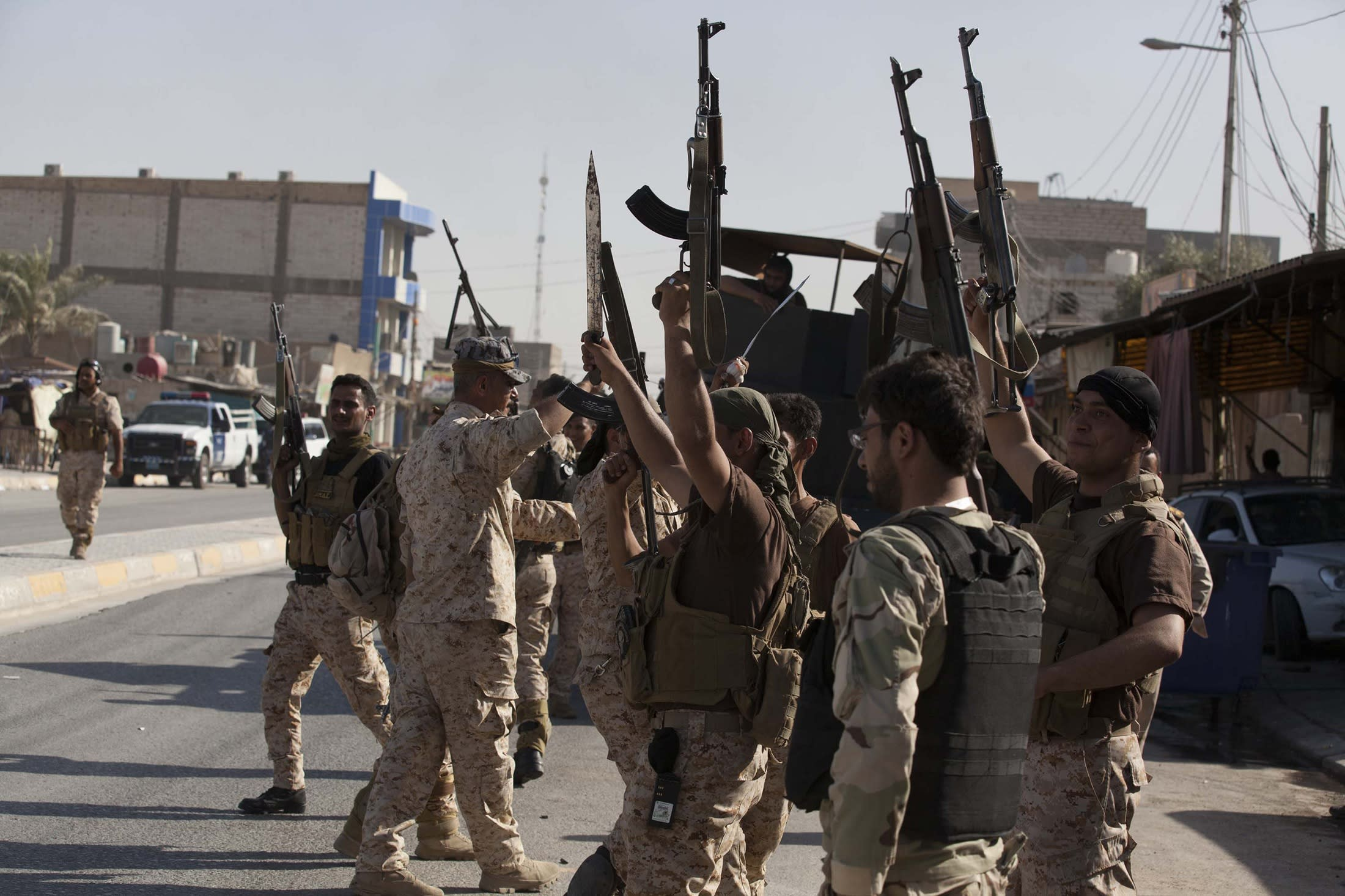 Members of the Iraqi security forces gesture after clashes with followers of Shi'ite cleric Sarkhi in Karbala