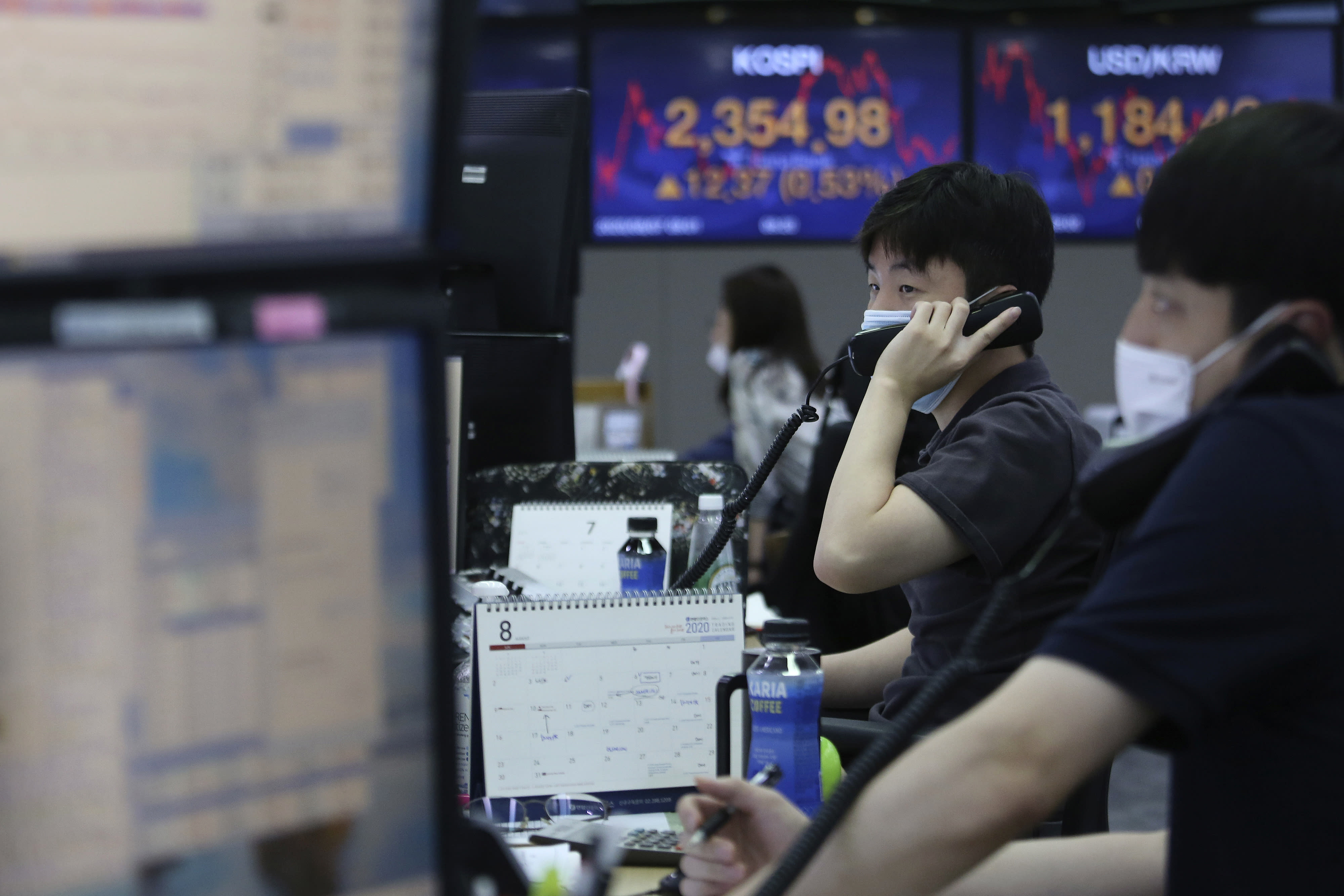Currency traders talk on phones at the foreign exchange dealing room of the KEB Hana Bank headquarters in Seoul, South Korea, Friday, Aug. 7, 2020. Asian shares were mostly lower Friday in lackluster trading, as the region weighed continuing trade tensions over China and optimism about more fiscal stimulus for the ailing U.S. economy. (AP Photo/Ahn Young-joon)