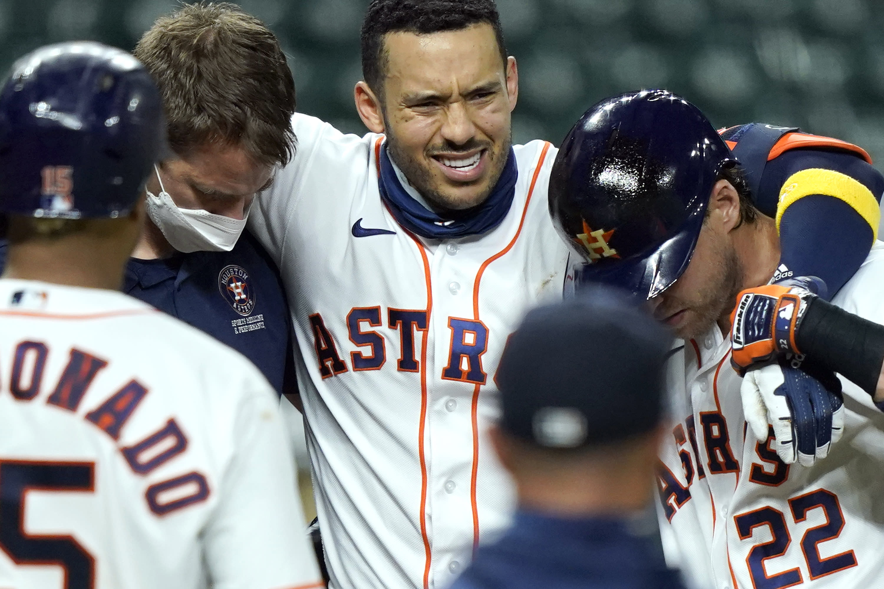 Houston Astros' Carlos Correa, center, is helped off the field after fouling a pitch off his leg during the sixth inning of a baseball game against the Texas Rangers Tuesday, Sept. 15, 2020, in Houston. (AP Photo/David J. Phillip)