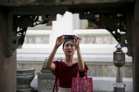 A tourist takes pictures inside a temple in Bangkok Thailand