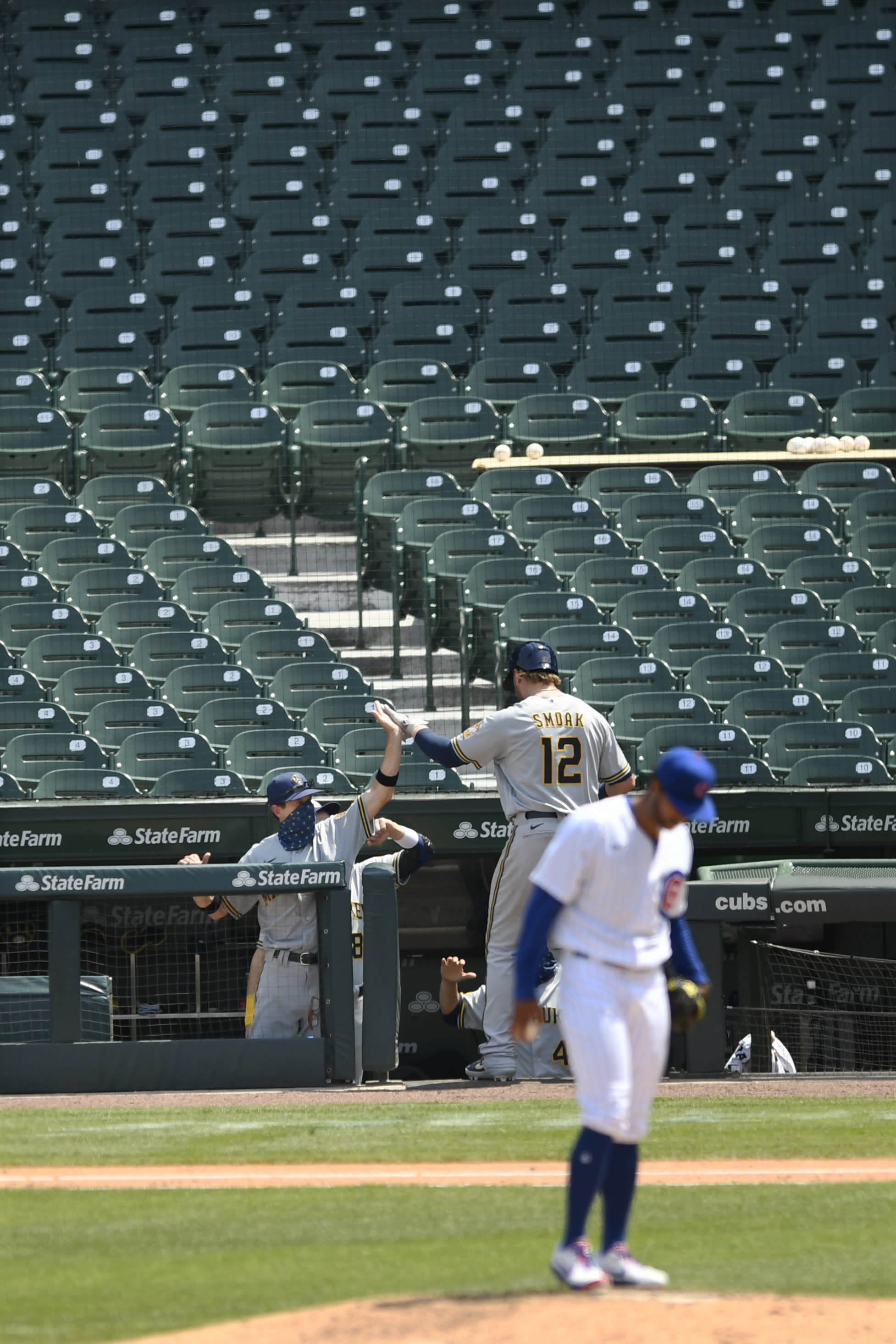 Milwaukee Brewers manager Craig Counsell left, celebrates with Justin Smoak (12) at the dugout after he hit a solo home run during the fifth inning of a baseball game against the Chicago Cubs Saturday, July 25, 2020, in Chicago. (AP Photo/Paul Beaty)
