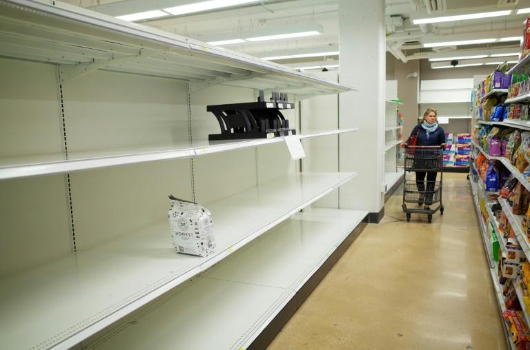 A shopper walks down an aisle with empty shelves for toilet paper at a Target store in Bethesda, Maryland on March 16, 2020 (AFP Photo/MANDEL NGAN)