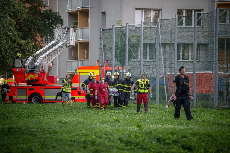 Firefighters carry a stretcher at the scene where a fire broke out in an apartment block in Bohumin, eastern Czech Republic on August 8, 2020