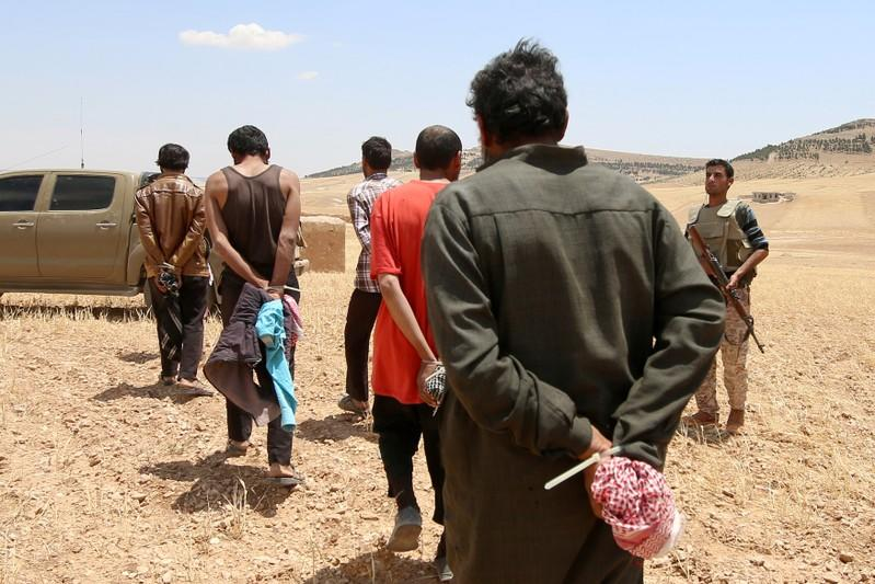 FILE PHOTO: Men, who the Democratic Forces of Syria fighters claimed were Islamic State fighters, walk as they are taken prisoners after SDF advanced in the southern rural area of Manbij