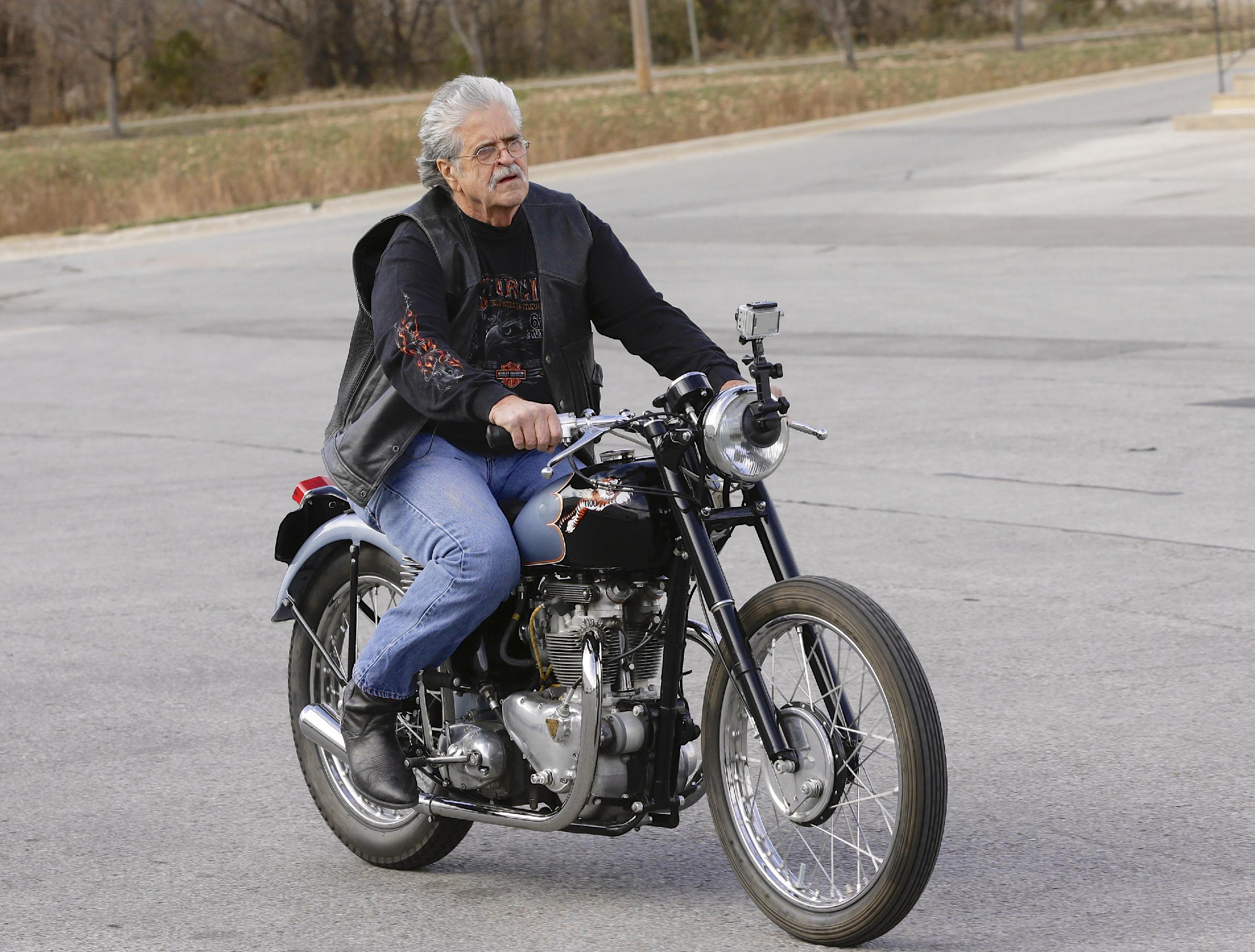 Donald DeVault, 73, rides his motorcycle in a parking lot in Omaha, Neb., after it was returned to him on Wednesday, Nov. 20, 2013. It was the first time he had seen the bike since it was stolen 46 years ago. California authorities had recovered his 1953 Triumph Tiger 100 at the Port of Los Angeles where it was about to be shipped to Japan. (AP Photo/Nati Harnik)