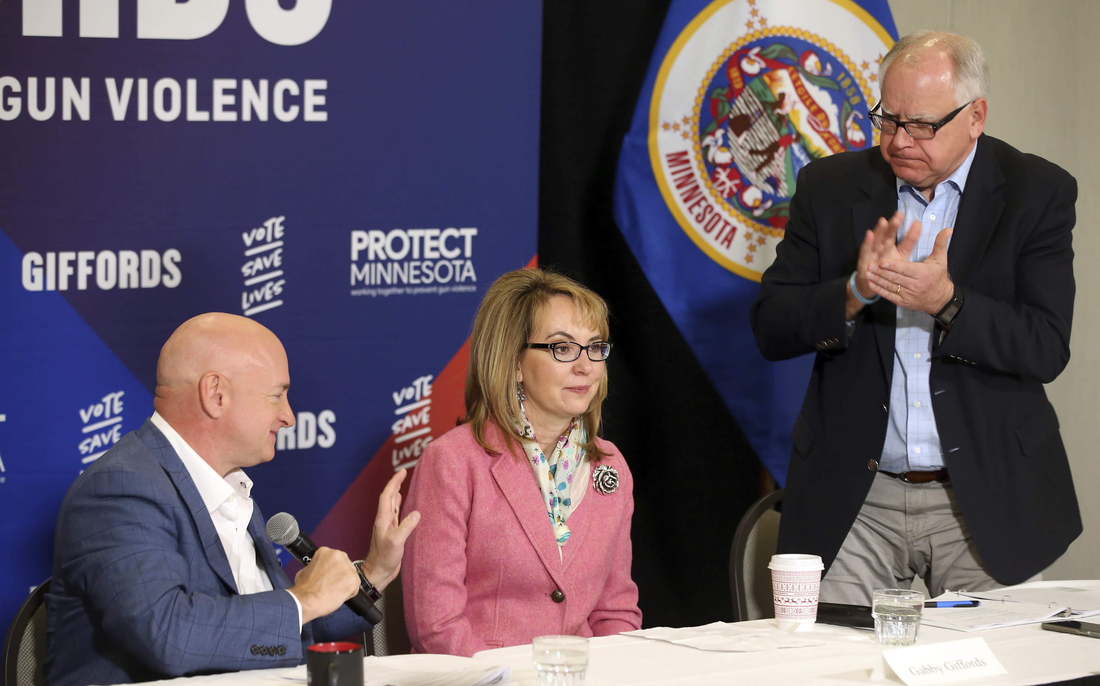 In this Oct. 26, 2018 photo, Minnesota gubernatorial candidate, Democrat Tim Walz, right, applauds as Capt. Mark Kelly, left, introduces his wife, former Rep. Gabby Giffords as they hosted a roundtable against gun violence in Minneapolis. The 2018 election marks the first time that groups supporting gun control measures could spend more on a campaign than the National Rifle Association. (AP Photo/Jim Mone)
