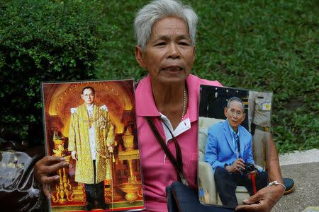 A well-wisher holds portraits of Thailand's King Bhumibol Adulyadej at Siriraj Hospital in Bangkok, Thailand, October 11, 2016. REUTERS/Chaiwat Subprasom