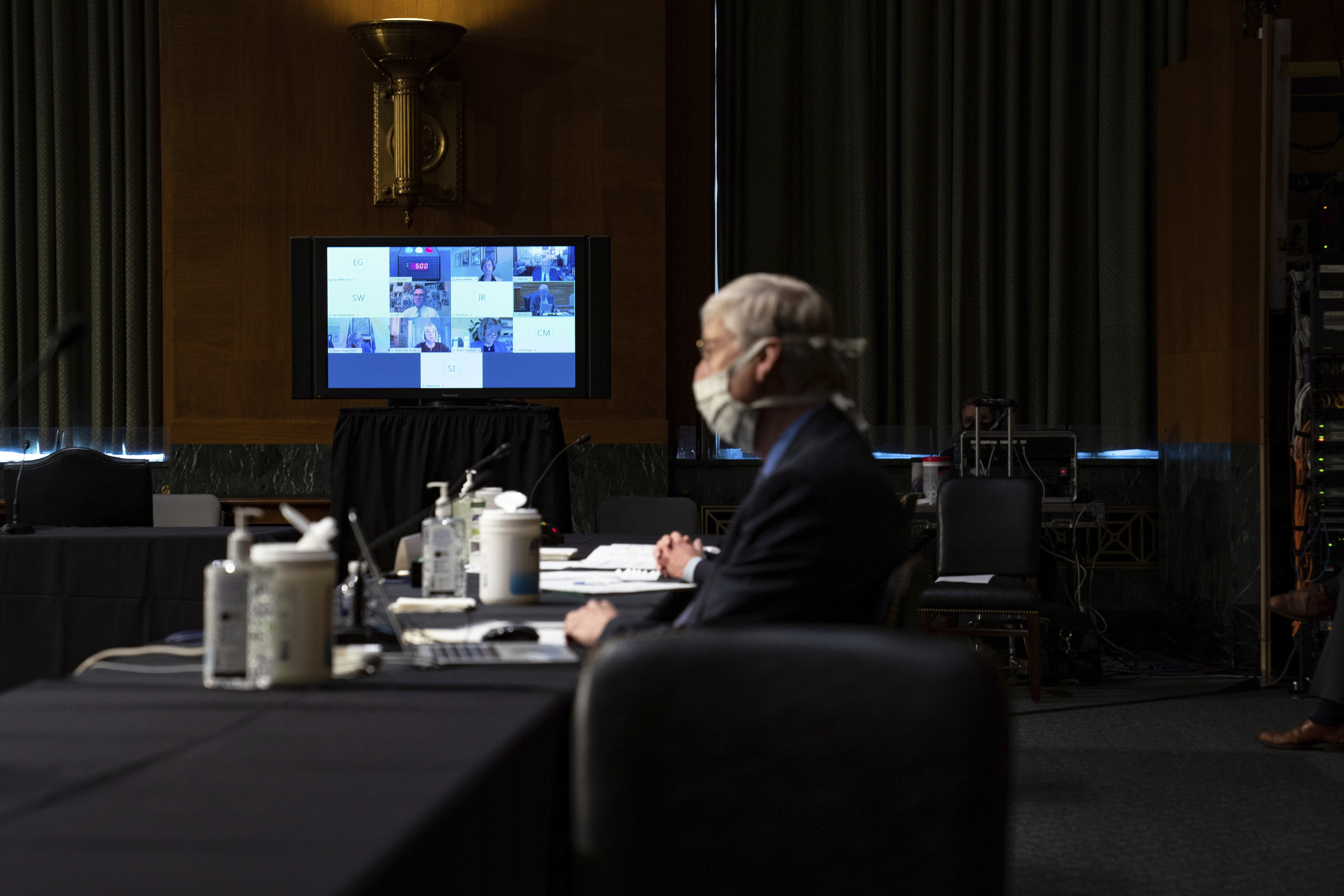 A monitor displays video feeds from members of the Senate Health Education Labor and Pensions Committee via teleconference during a Senate Health Education Labor and Pensions Committee hearing on new coronavirus tests on Capitol Hill in Washington, Thursday, May 7, 2020. National Institutes of Health Director Dr. Francis Collins, looks on at right. (Anna Moneymaker/The New York Times via AP, Pool)