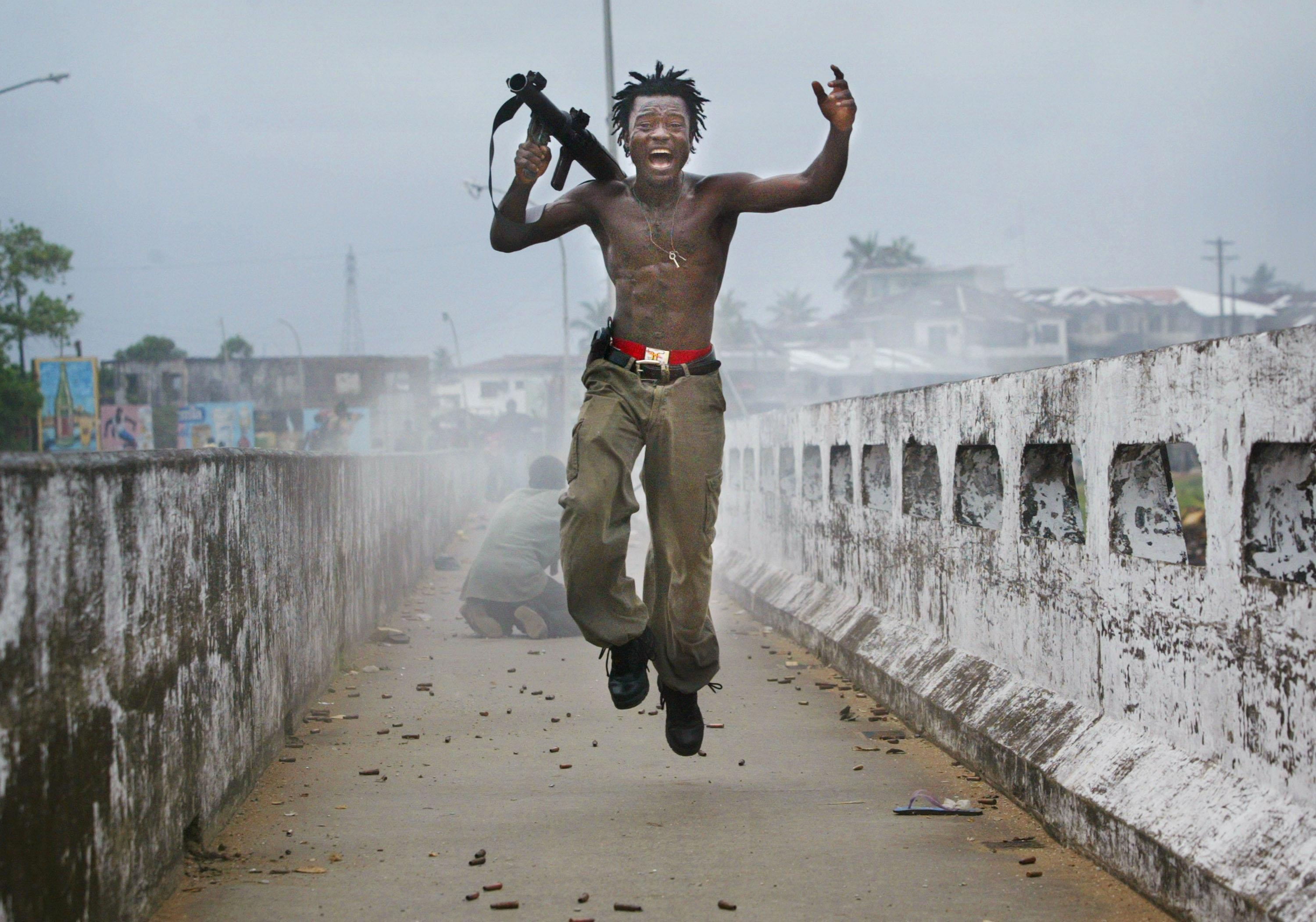 <p>A Liberian militia commander loyal to the government exults after firing a rocket-propelled grenade at rebel forces at a key strategic bridge July 20, 2003 in Monrovia, Liberia. Government forces succeeded in forcing back rebel forces in fierce fighting on the edge of Monrovia's city center. </p>
