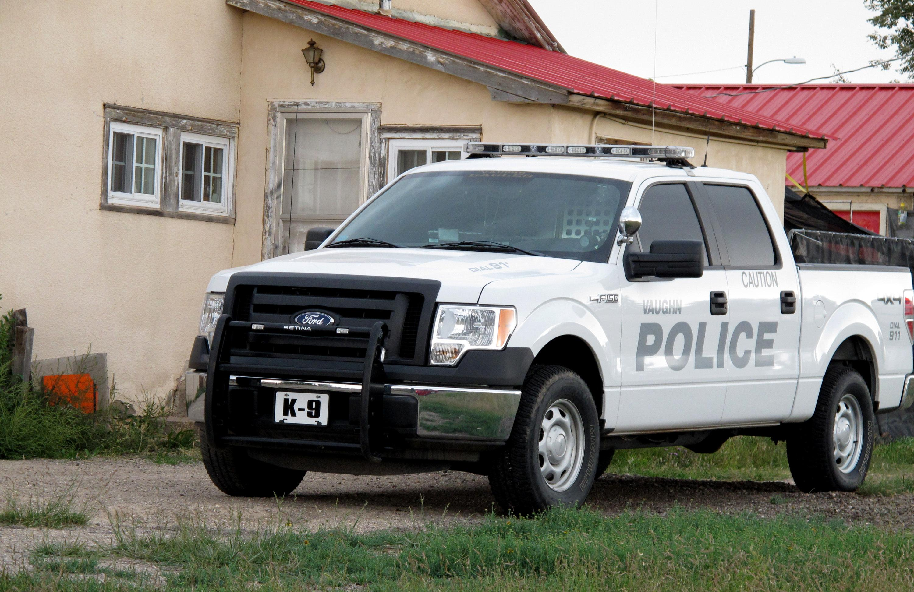 """The """"K-9"""" police truck of the Vaughn, N.M. Police Department is shown in driveway of former Vaughn Police Chief Ernest """"Chris"""" Armijo Wednesday, Sept. 26, 2012 photo. Vaughn officials announced Wednesday that Armijo resigned after news stories reported that he was not allowed to carry a gun due to his criminal record, leaving the town with just one certified member on its police- force a drug-sniffing dog named Nikka. The town's only other officer isn't certified and pleaded guilty to charges of assault and battery last year. (AP Photo/Russell Contreras)"""