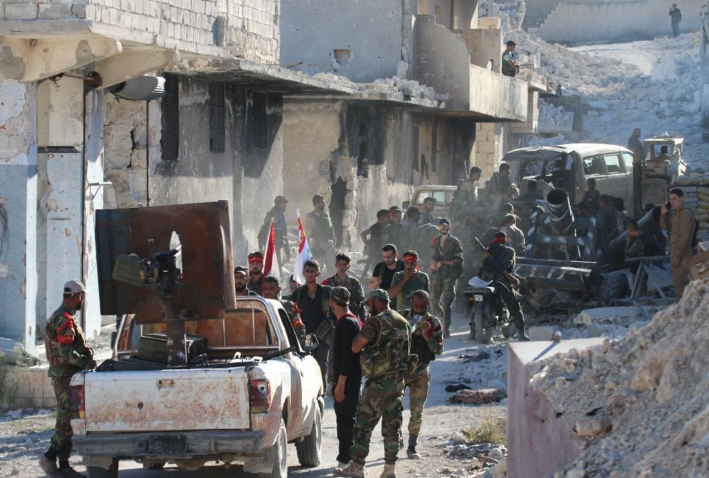 Syrian government forces gather amidst destruction in the largely deserted Palestinian refugee camp of Handarat, north of Aleppo (AFP Photo/George Ourfalian)