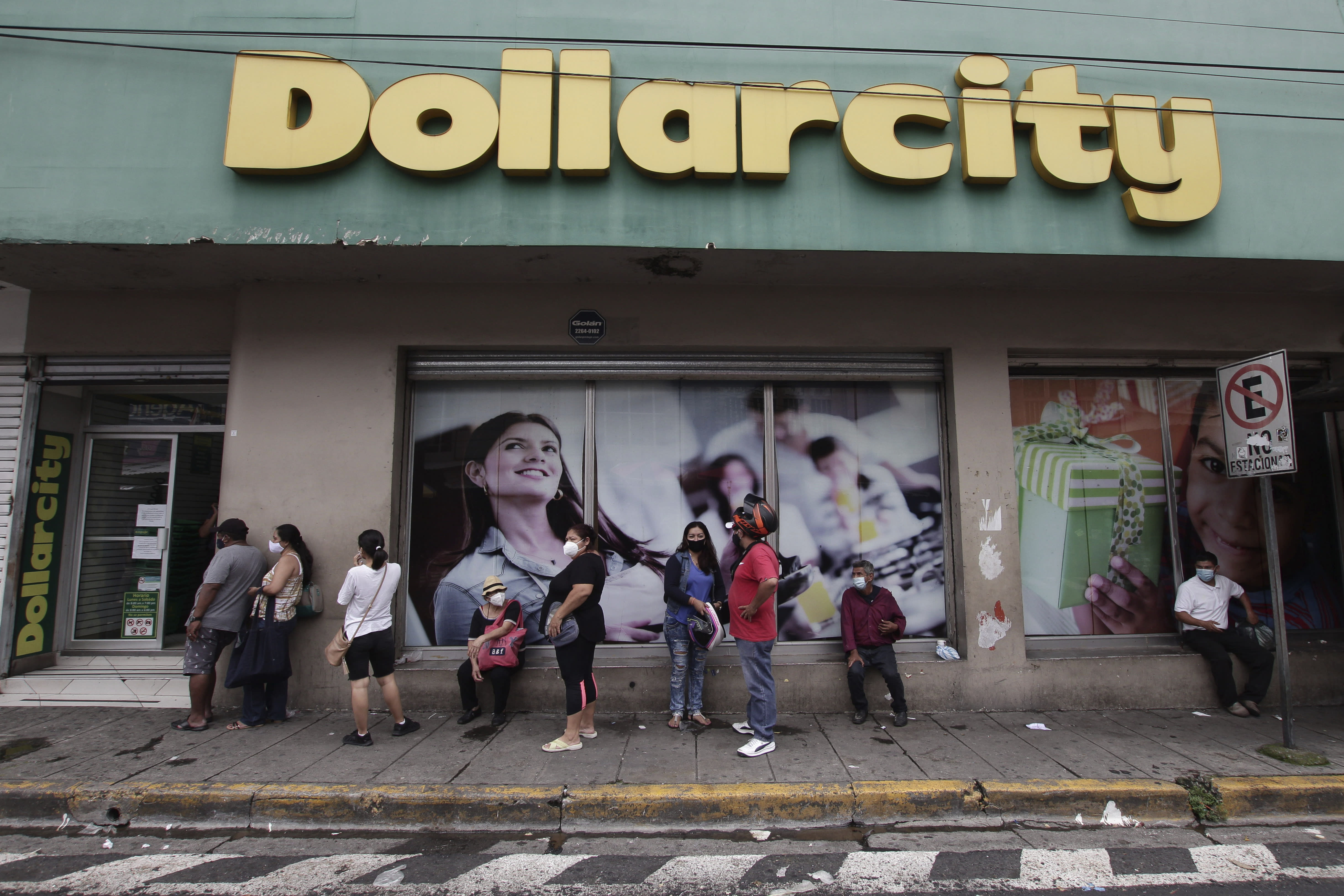 Shoppers, wearing protective face masks, form a line outside Dollarcity in San Salvador, El Salvador, Thursday, Aug. 6, 2020, amid the new coronavirus pandemic. For months, the strictest measures confronting the COVID-19 pandemic in Latin America seemed to keep infections in check in El Salvador, but a gradual reopening combined with a political stalemate has seen infections increase nearly fourfold. (AP Photo/Salvador Melendez)