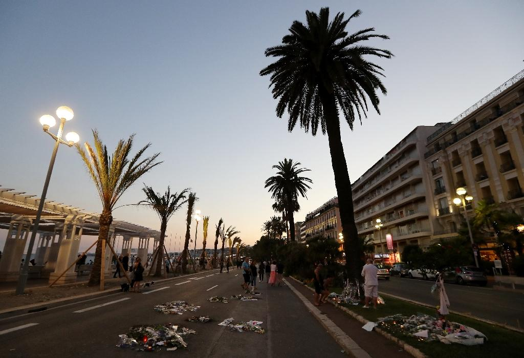 People walk past flowers, candles and messages laid on the Promenade des Anglais seafront in Nice on July 18, 2016, in tribute to the victims of the deadly attack which killed 84 people on July 14 (AFP Photo/Valery Hache)