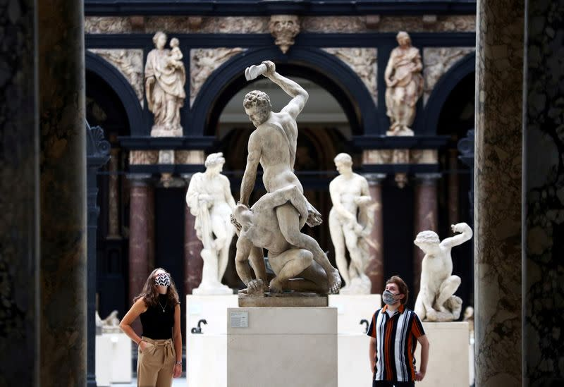 Victoria & Albert (V&A) Museum gallery assistants pose for members of the media in front of the 'Samson Slaying a Philistine' sculpture during preparations to reopen the museum, in London