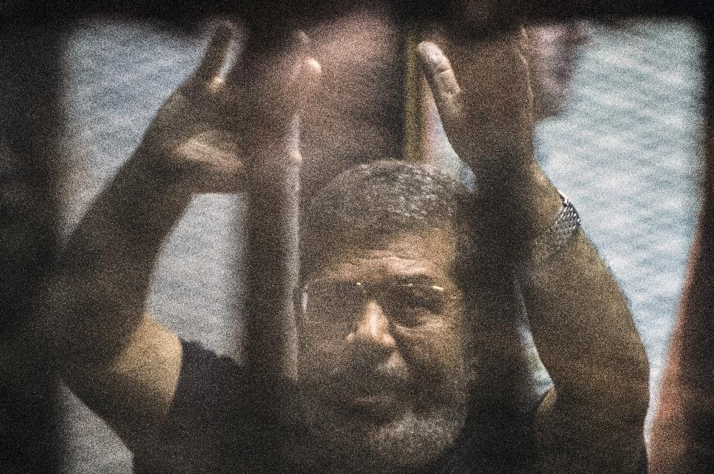 Egypt's deposed Islamist president Mohamed Morsi raises his hands from behind the defendant's cage as the judge reads out his verdict in Cairo on May 16, 2015 (AFP Photo/Khaled Desouki)