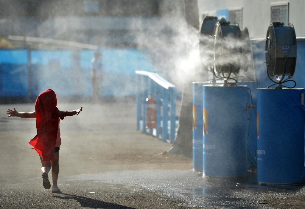 A young child cools off by running past a set of vapour fans in Melbourne (AFP Photo/PETER PARKS)