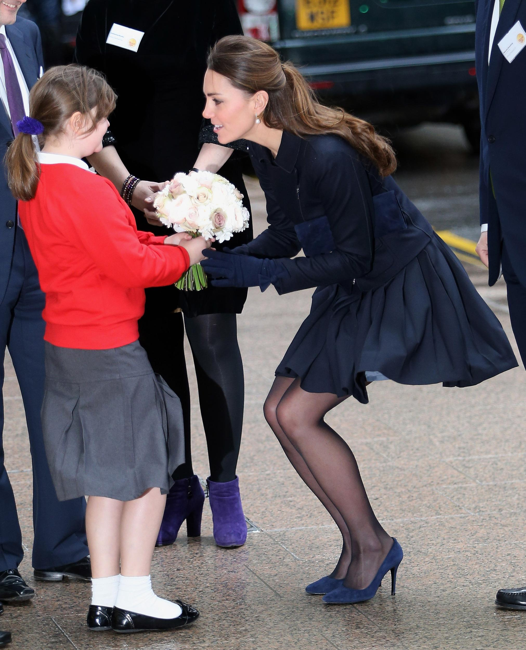 Kate looked lovely in London, wearing an Orla Kiely skirt and MaxMara coat as she received flowers from a young girl.