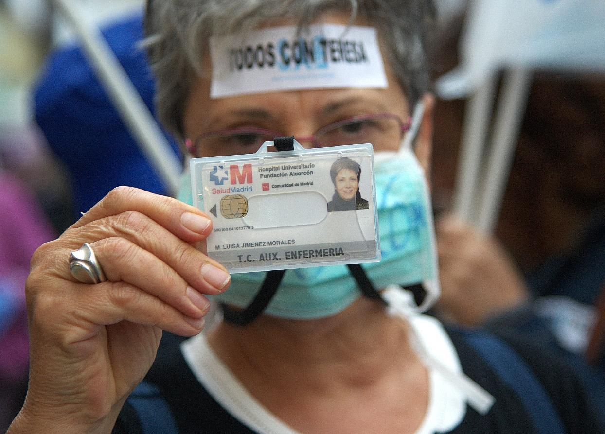 A protester holds her nurse identification card during a demonstration in support of Spanish nurse Teresa Romero infected with the deadly Ebola virus in Madrid on October 11, 2014