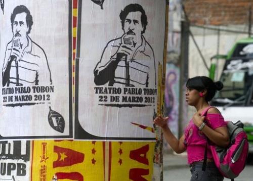 Una mujer pasa junto a unos carteles con la imagen de Pablo Escobar en Medellín