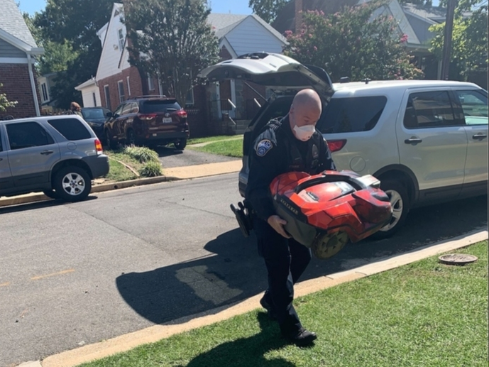 An Arlington County Police officer returns Shultzy the AutoMower back to his Maywood home, after someone had walked off with him on Tuesday morning.
