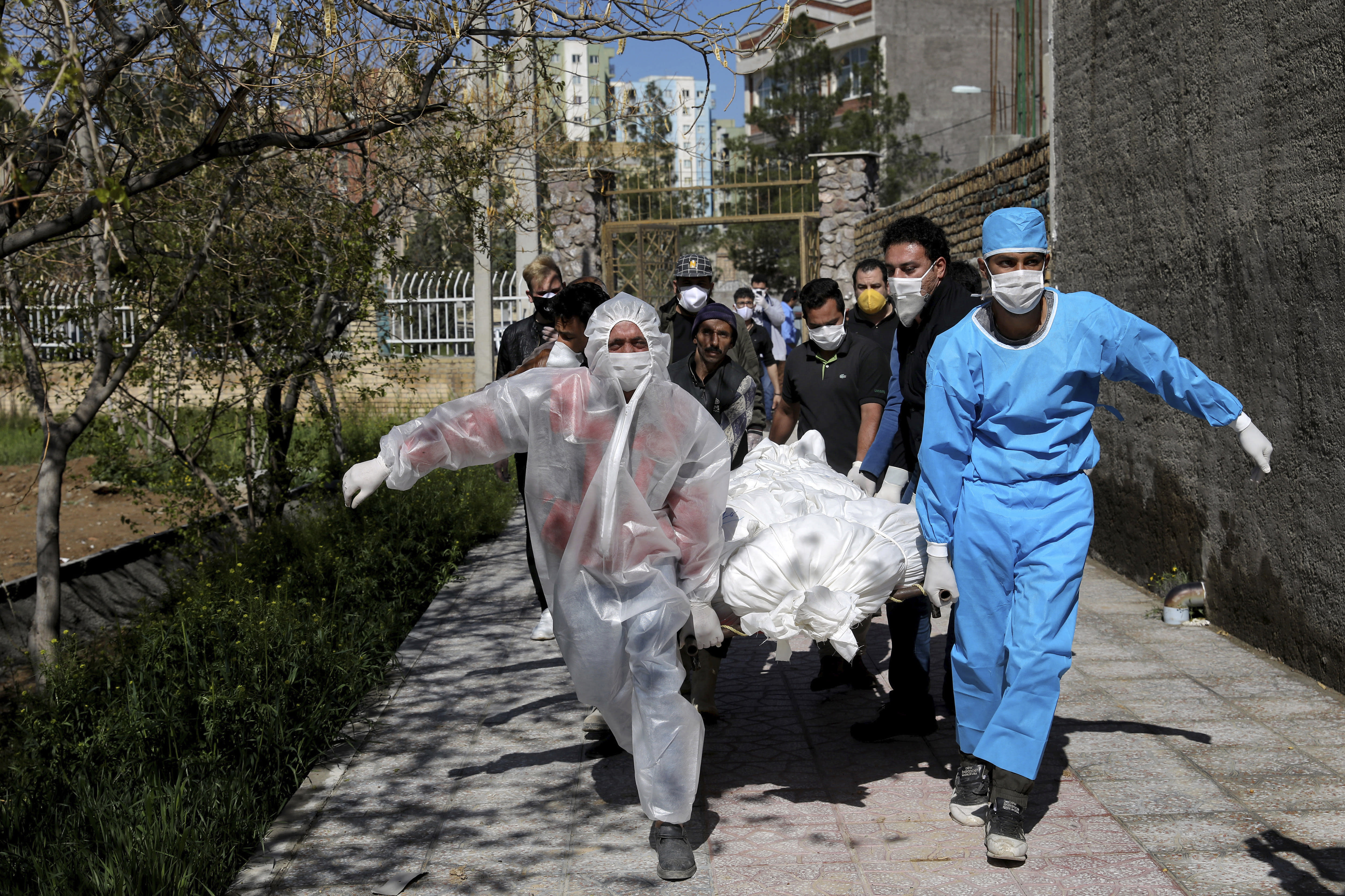 FILE - In this Monday, March 30, 2020 file photo, people carry the body of a victim who died after being infected with the new coronavirus at a cemetery just outside Tehran, Iran. Across the Middle East and parts of South Asia, bereaved families have faced traumatic restrictions on burying their dead amid the pandemic. Religion and customs that require speedy burials in the largely Muslim region have clashed with fears of COVID-19 contagion and government-mandated lockdowns. (AP Photo/Ebrahim Noroozi, File)