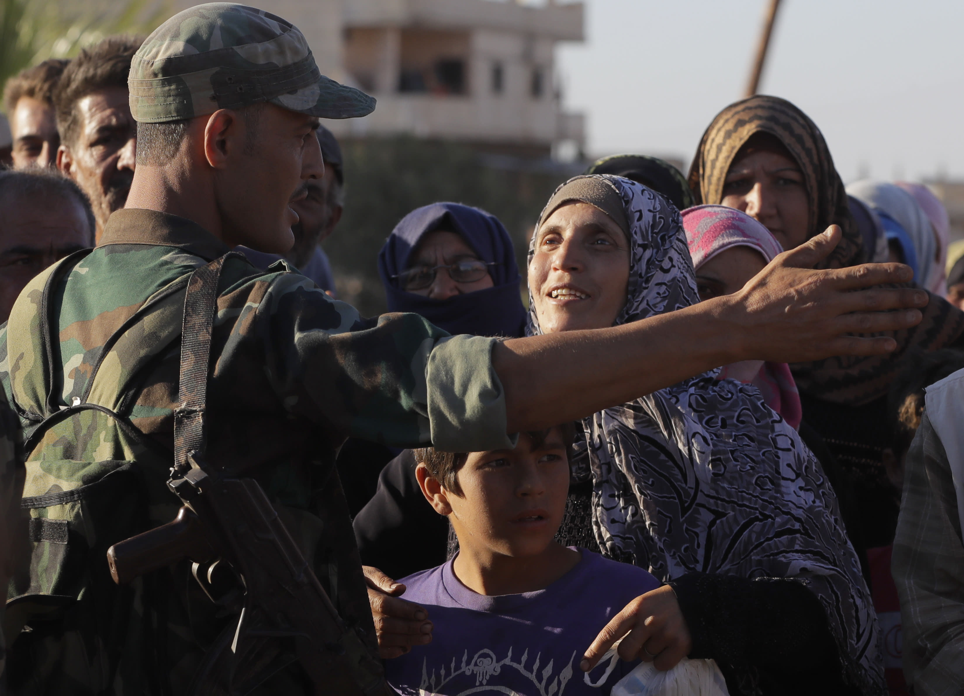 FILE - In this Aug. 15, 2018 file photo, a woman talks with a soldier of the Syrian army during distribution of humanitarian aid from the Russian military in the town of Rastan, Syria. Over the last two days, members of the UN Security Council have been haggling over cross-border aid delivery to Syria, with Russia, a major ally of the Syria government, working to reduce the delivery of U.N. humanitarian aid to Syria's last rebel-held northwest down from two crossings to just one. A final vote is expected Friday, July 10, 2020 as western countries push on a new resolution to keep the two crossings open for six months, instead of a year. (AP Photo/Sergei Grits, File)