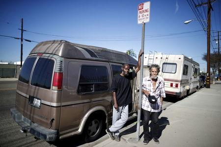Bernard Leatherwood, 62, (L) and his friend Arthur Johnson, 72, pose for a portrait next to the motorhome in which they live on the streets of Los Angeles, California, United States, November 12, 2015. REUTERS/Lucy Nicholson