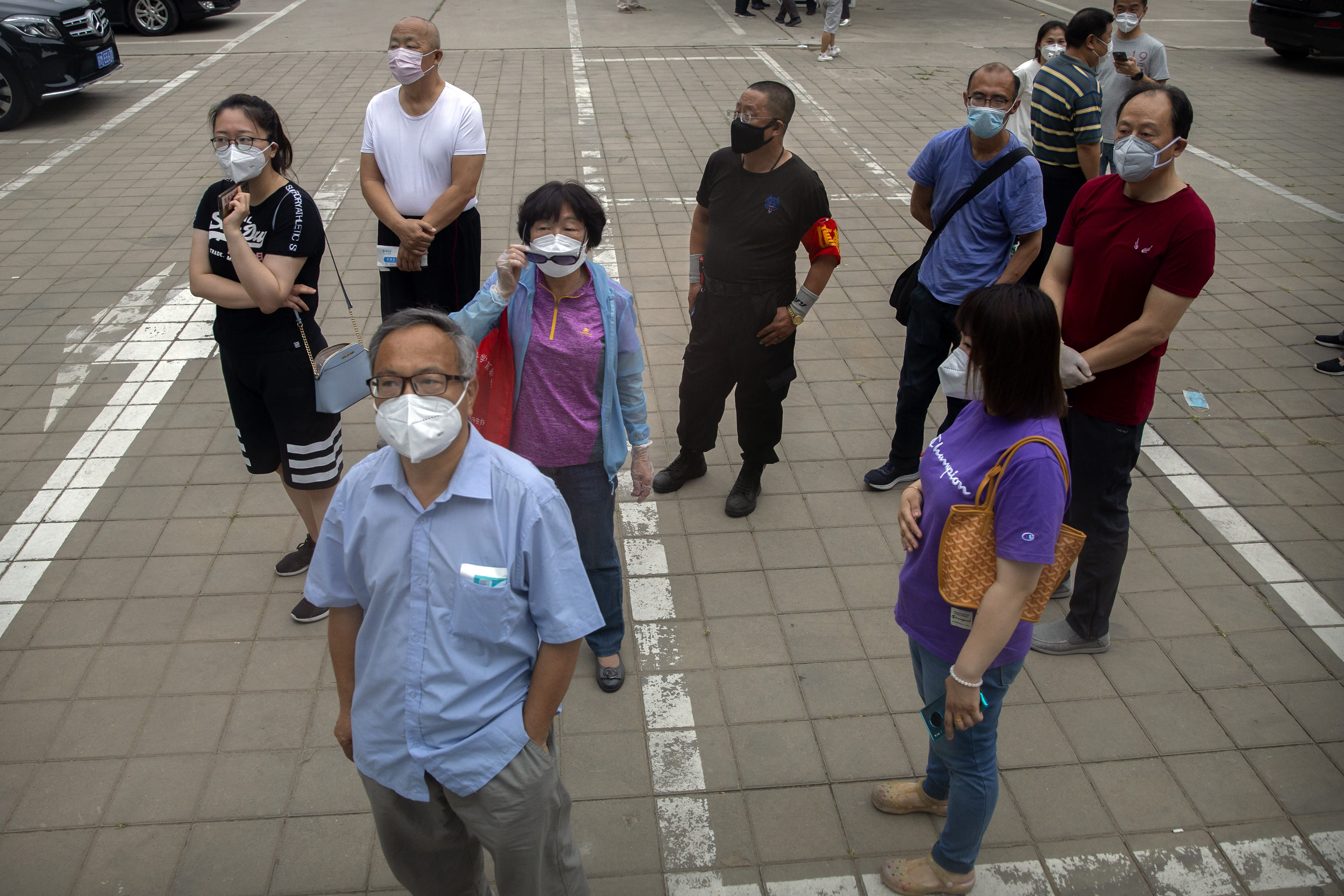 People wearing face masks watch as a bus of tested patients leaves a COVID-19 testing site for those who were potentially exposed to the coronavirus outbreak at a wholesale food market in Beijing, Wednesday, June 17, 2020. As the number of cases of COVID-19 in Beijing climbed in recent days following an outbreak linked to a wholesale food market, officials announced they had identified hundreds of thousands of people who needed to be tested for the coronavirus. (AP Photo/Mark Schiefelbein)