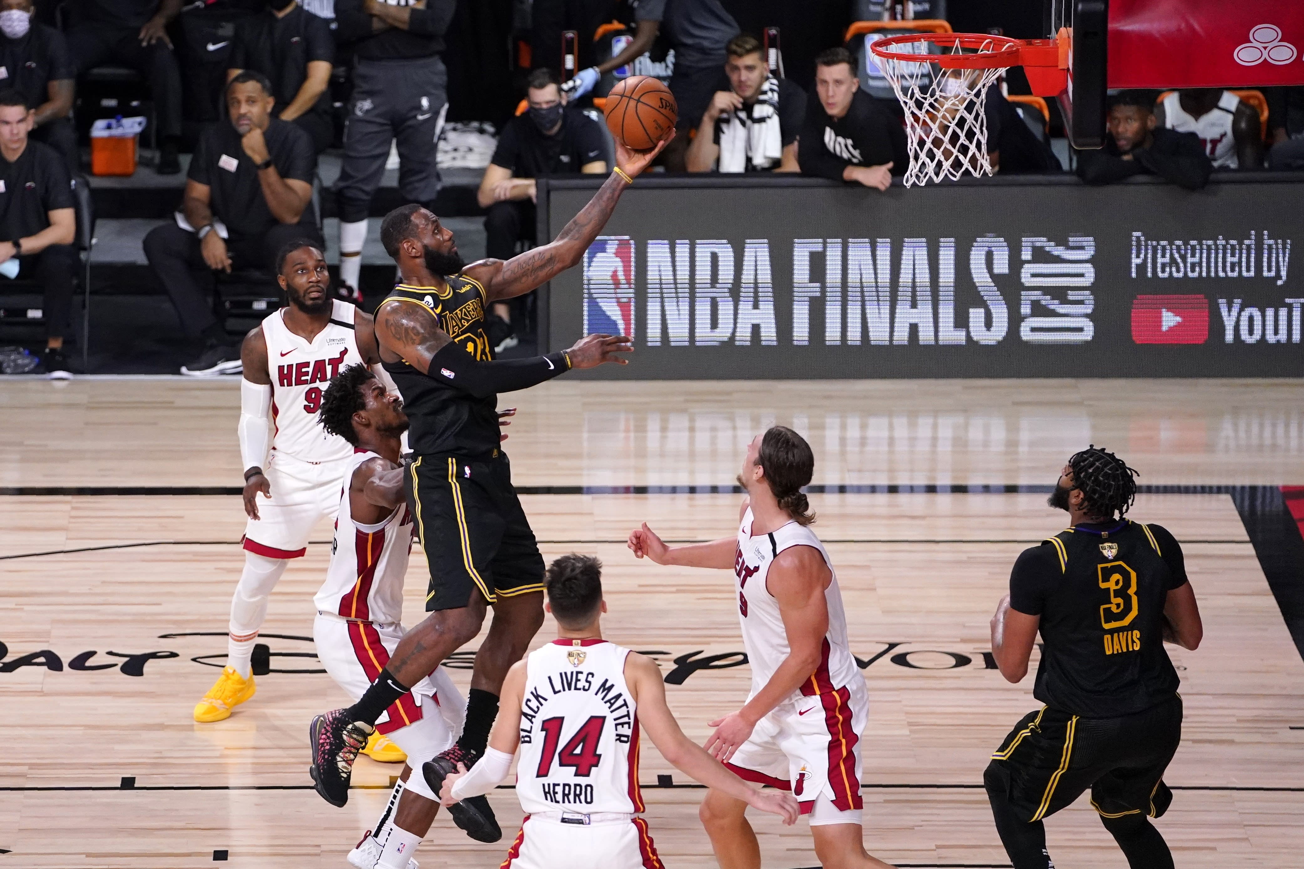 Los Angeles Lakers forward LeBron James (23) goes up for a shot between Miami Heat's Jimmy Butler, center left, Tyler Herro (14), and Kelly Olynyk (9) during the second half of Game 2 of basketball's NBA Finals, Friday, Oct. 2, 2020, in Lake Buena Vista, Fla. (AP Photo/Mark J. Terrill)