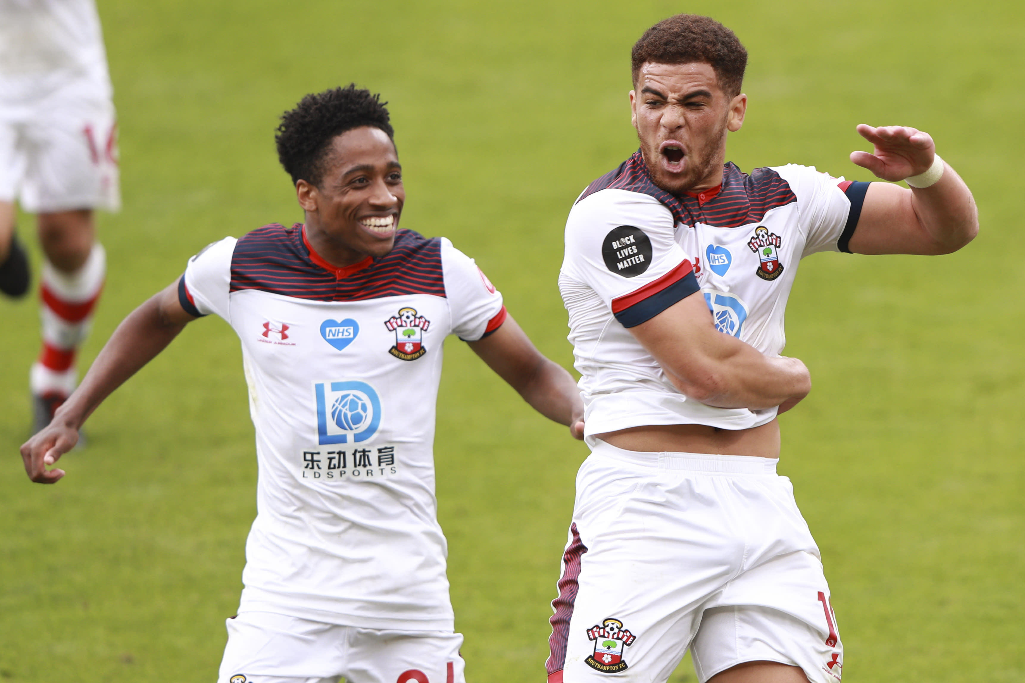 Southampton's Che Adams, right, celebrates with Kyle Walker-Peters after scoring his side's second goal during the English Premier League soccer match between Bournemouth and Southampton at Vitality Stadium in Bournemouth, England, Sunday, July 19, 2020. (Ian Walton/Pool Photo via AP)