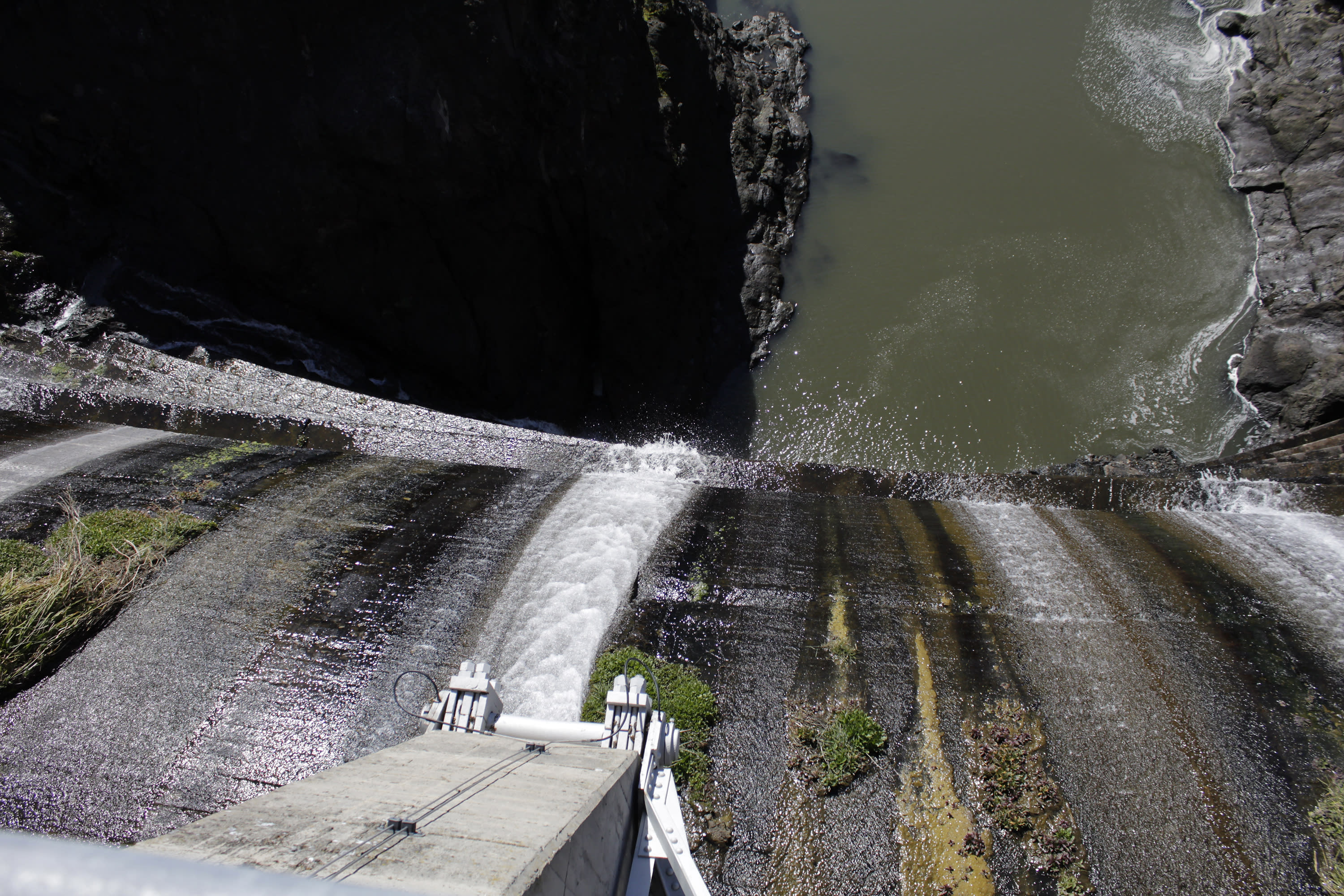 FILE - In this March 3, 2020 file photo, excess water spills over the top of a dam on the lower Klamath River known as Copco 1 near Hornbrook, Calif. A plan to demolish four dams on California's second-largest river to benefit threatened salmon has sharpened a decades-old dispute over who has the biggest claim to the river's life-giving waters. Federal regulators on Thursday, July 16, 2020, threw a significant curveball at a coalition that has been planning for years to demolish four massive hydroelectric dams on a river along the Oregon-California border to save salmon. (AP Photo/Gillian Flaccus, File)