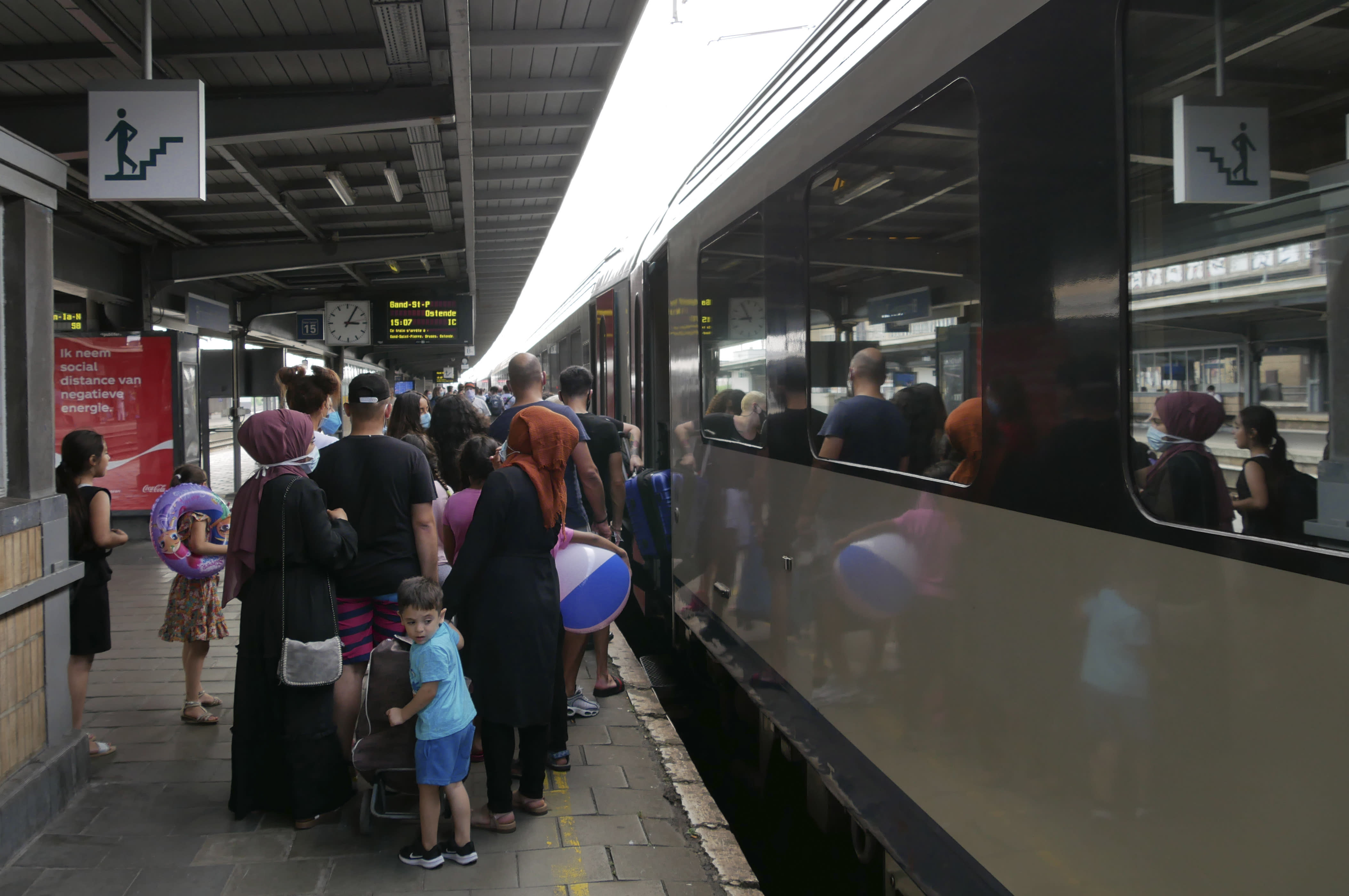People wait to board a train in Brussels to the Belgian coastal resort of Blankenberge, Belgium on Tuesday, Aug. 11, 2020. The coast is just a 90-minute train ride from the capital Brussels, and other places where people who seldom have cars could get away from it all and cool off are poorly served by public transport. Many youths were boarding trains in Brussels Tuesday, but Knokke-Heist station was almost empty. (AP Photo/Sylvain Plazy)