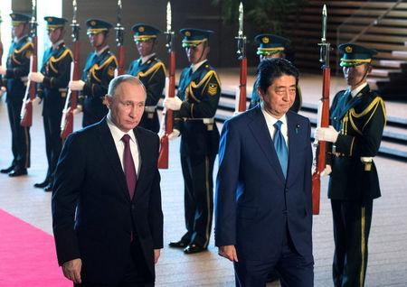 Russian President Vladimir Putin (L) and Japanese Prime Minister Shinzo Abe review the guard of honour during a meeting in Tokyo, Japan, December 16, 2016. Sputnik/Sergey Guneev/Kremlin/via REUTERS
