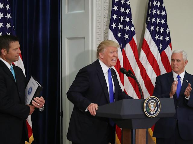 Donald Trump speaks while flanked by Kansas Secretary of State, Kris Kobach and US Vice President Mike Pence during the first meeting of the Presidential Advisory Commission on Election Integrity on 19 July 2017: Mark Wilson/Getty Images