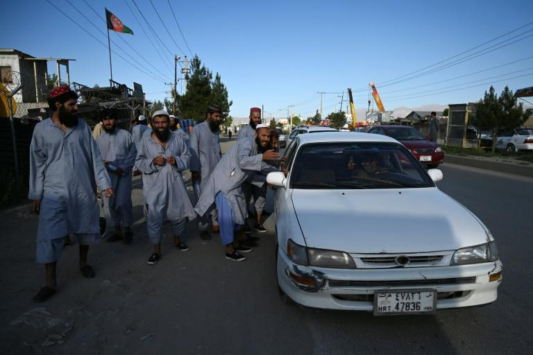 Taliban prisoners stop a local taxi after their release from Afghanistan's Bagram prison (AFP Photo/WAKIL KOHSAR)