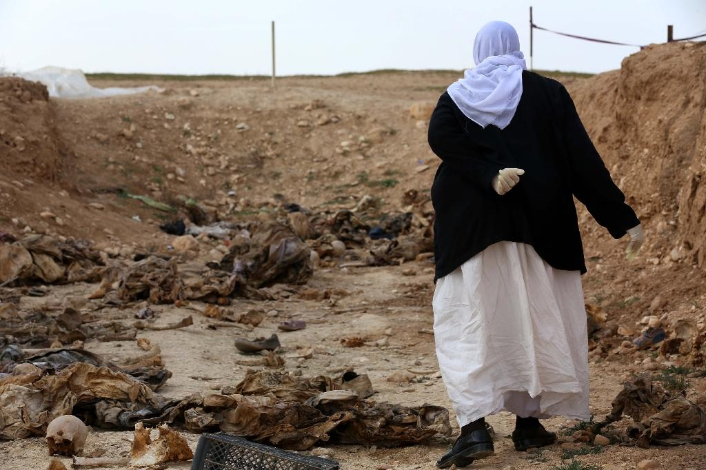 A member of the Yazidi minority searches for clues on February 3, 2015 that might lead her to missing relatives, among the remains of people killed by the Islamic State group