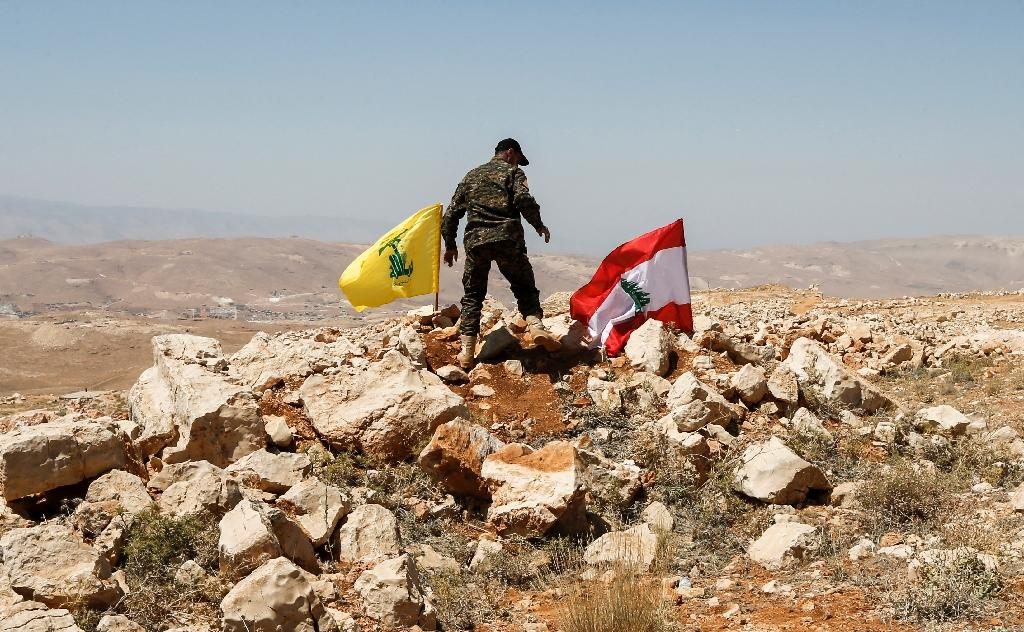 A picture taken on an escorted tour by the Lebanese Shiite Hezbollah movement shows a fighter planting the group's flag and the Lebanese national flag in the Lebanese border area of Jurud Arsal on July 26, 2017 (AFP Photo/ANWAR AMRO)