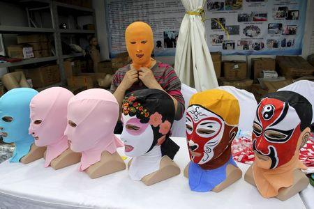 Zhang Shifan tries on a face-kini mask as she demonstrates her products at an exhibition in Qingdao, Shandong province, China, May 22, 2015. REUTERS/Stringer