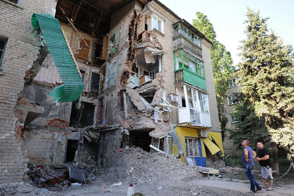 Men look at a building destroyed by the Ukrainian Air Force in Snezhnoye, 80 km east of Donetsk, on July 16, 2014 (AFP Photo/Dominique Faget)