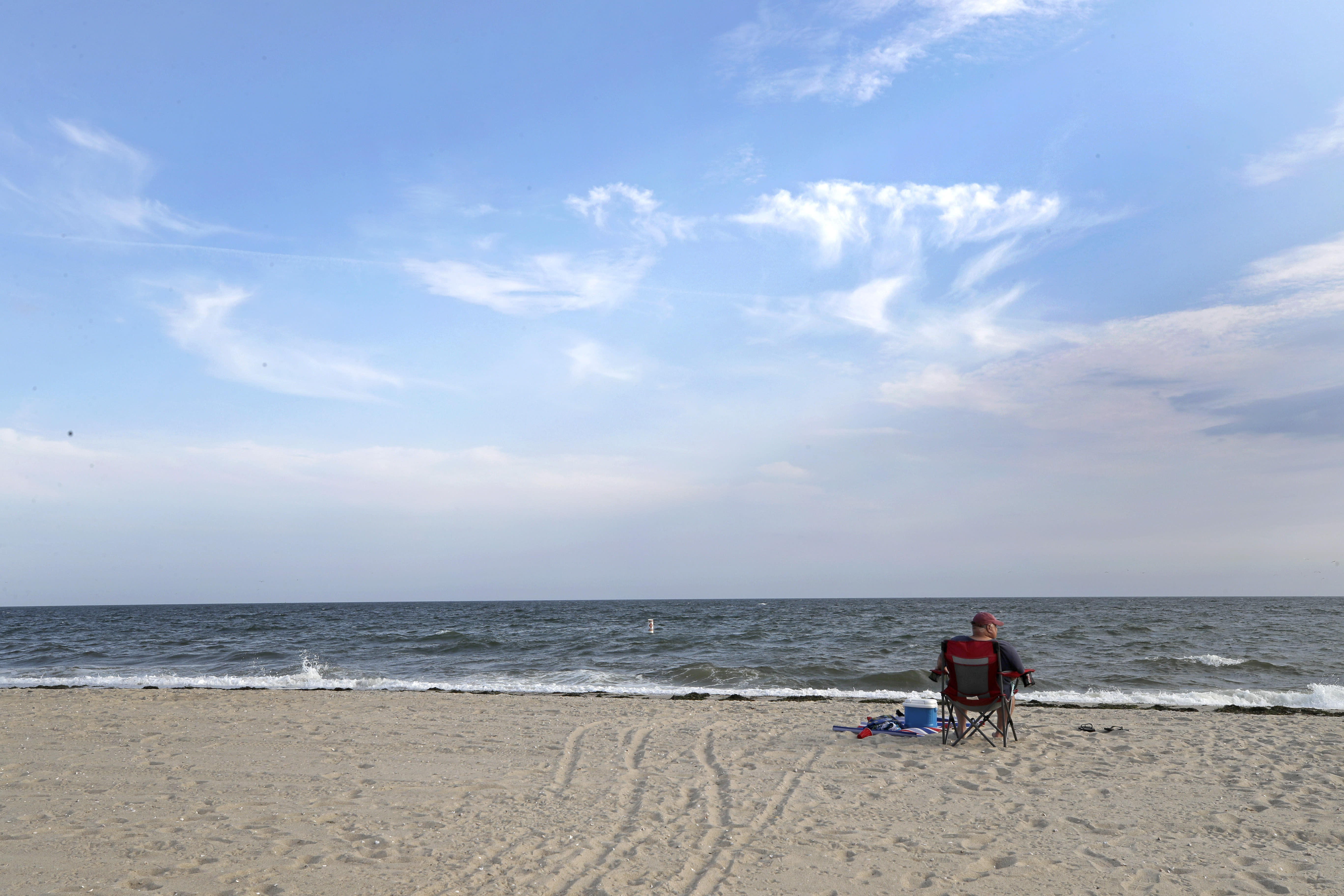In this Aug. 21, 2019 photo, a man enjoys the view at Covell Beach in Centerville, Mass. Vineyard Winds' proposed buried energy cables would stretch from offshore wind turbines, through the ocean, under the sand and parking lot at Covell Beach, to a landing point where the cables would then extend to a grid connection inland. But as Trump has made clear how much he hates wind turbines, all the offshore wind projects, including the nation's first utility-scale offshore wind project, an 84 turbine, $2.8 billion wind farm slated to rise 15 miles off Martha's Vineyard, have stalled. (AP Photo/Elise Amendola)