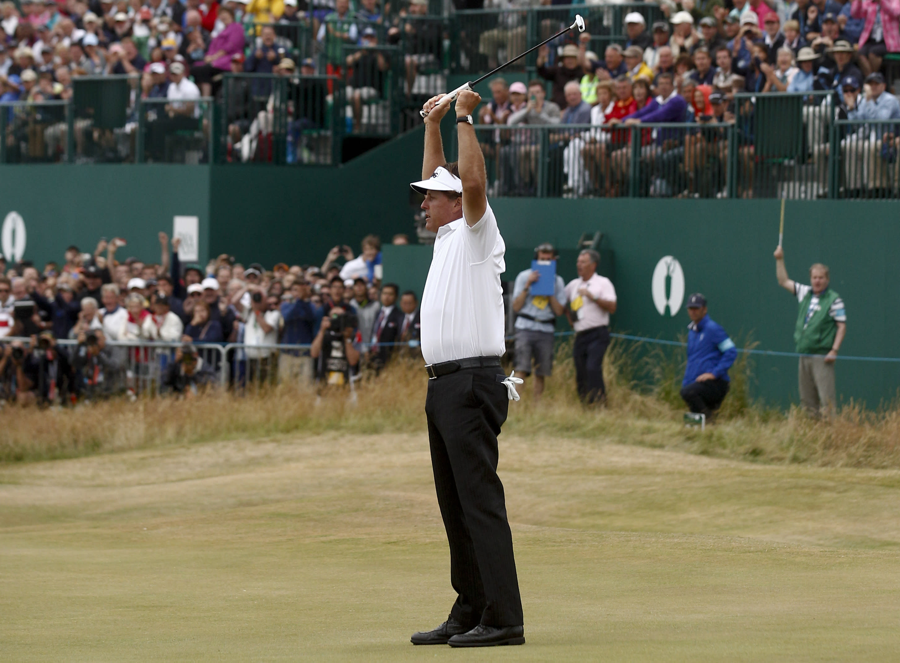 Phil Mickelson of the United States celebrates after his final putt on the 18th green during the final round of the British Open Golf Championship at Muirfield, in Gullane, Scotland, Sunday, July 21, 2013. (AP Photo/Jon Super)