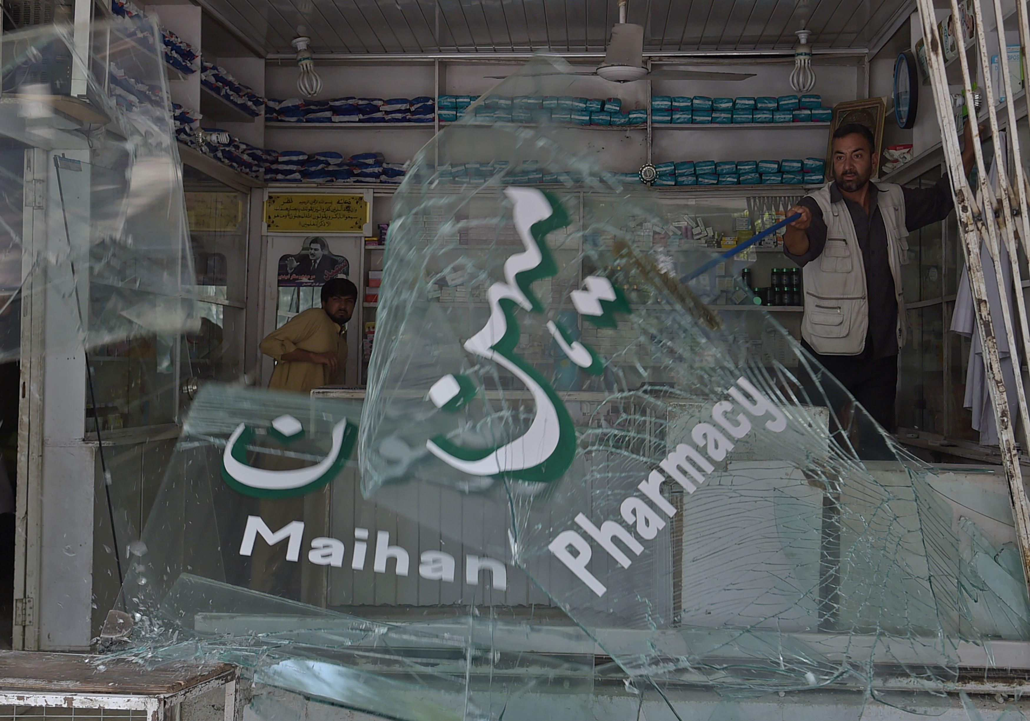 <p>Afghan shopkeepers clean up broken glass at the site of a suicide attack outside a bank near the U.S. embassy in Kabul on Aug. 29, 2017. A suicide bomber blew himself up on a busy shopping street near the US embassy in central Kabul on August 29, killing four people and injuring several others, officials said. It was the latest in a series of deadly attacks to hit the Afghan capital, and comes three months after a massive truck bomb ripped through the same area, killing about 150 people. (Photo: Shah Marai/AFP/Getty Images) </p>