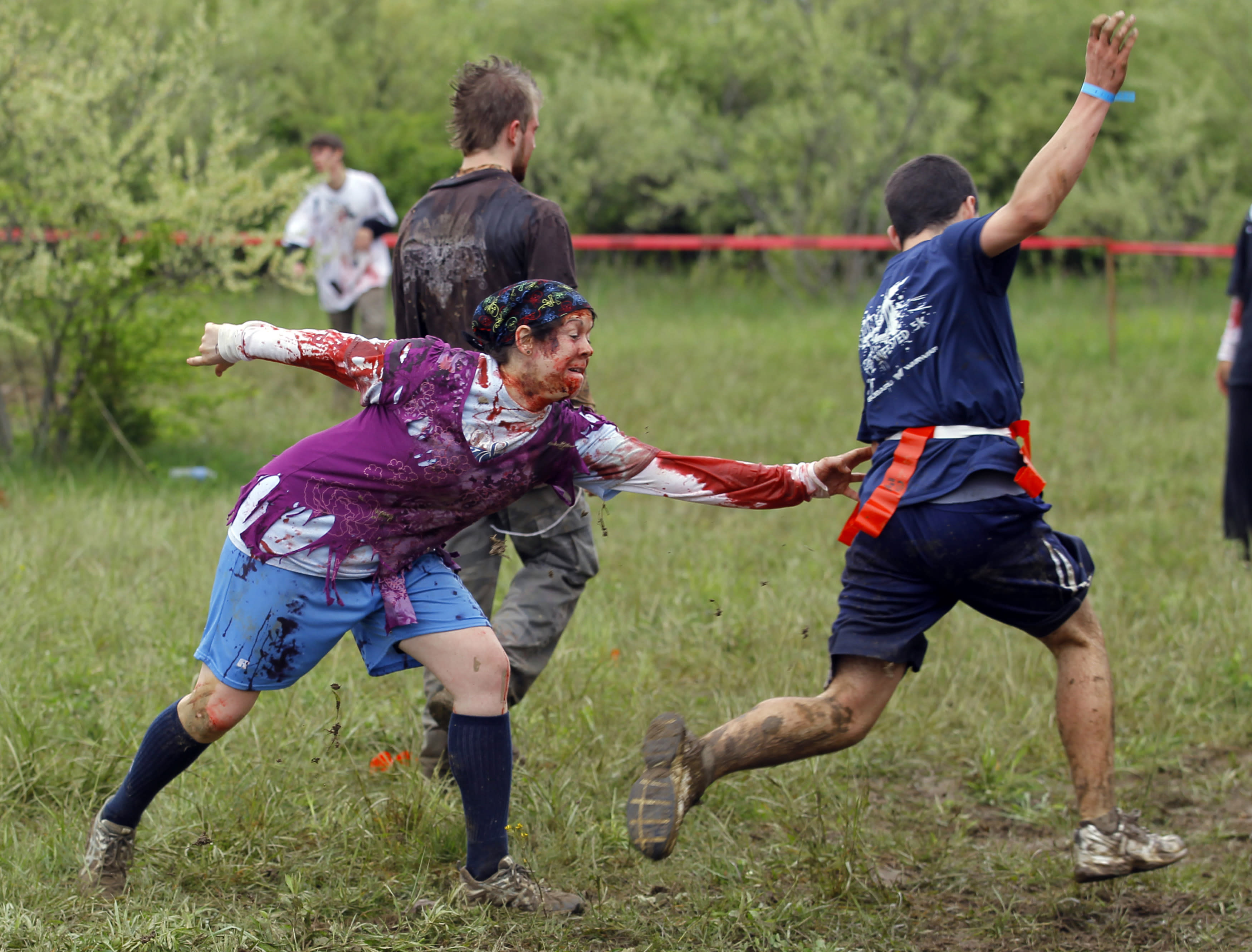 """A zombie chases a runner (R) on the """"Run for Your Lives"""" 5K obstacle course race in Amesbury, Massachusetts May 5, 2012. Runners face man-made and natural obstacles on the course, while being chased by zombies, who try to take """"health"""" flags off the runners belts. REUTERS/Brian Snyder"""