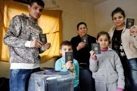 Iraqi refugee Nizar Kassab and his family pose for pictures with their passports in their temporary home in Beirut, Lebanon February 4, 2017. REUTERS/ Jamal Saidi