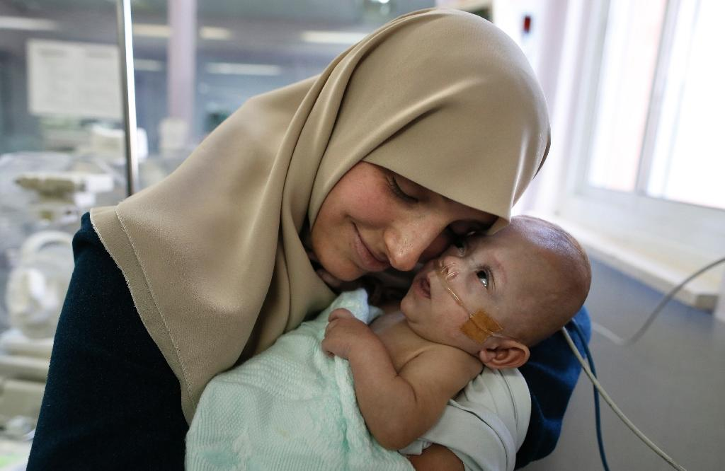 Gazan Jumana Daoud carries her 7-month-old daughter Maryam at Makassed Hospital in Israeli-annexed east Jerusalem on February 20, 2017, as they meet for the first time since the baby's premature birth (AFP Photo/AHMAD GHARABLI)